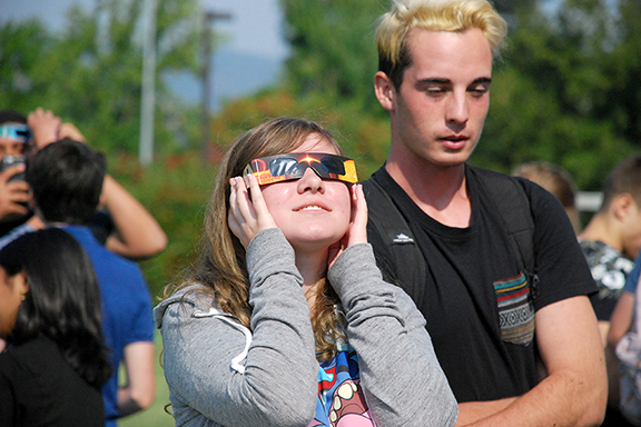 Senior Katie Jimerson views the eclipse through the protective glasses while Clayton Ballman avoids retina damage by looking down.