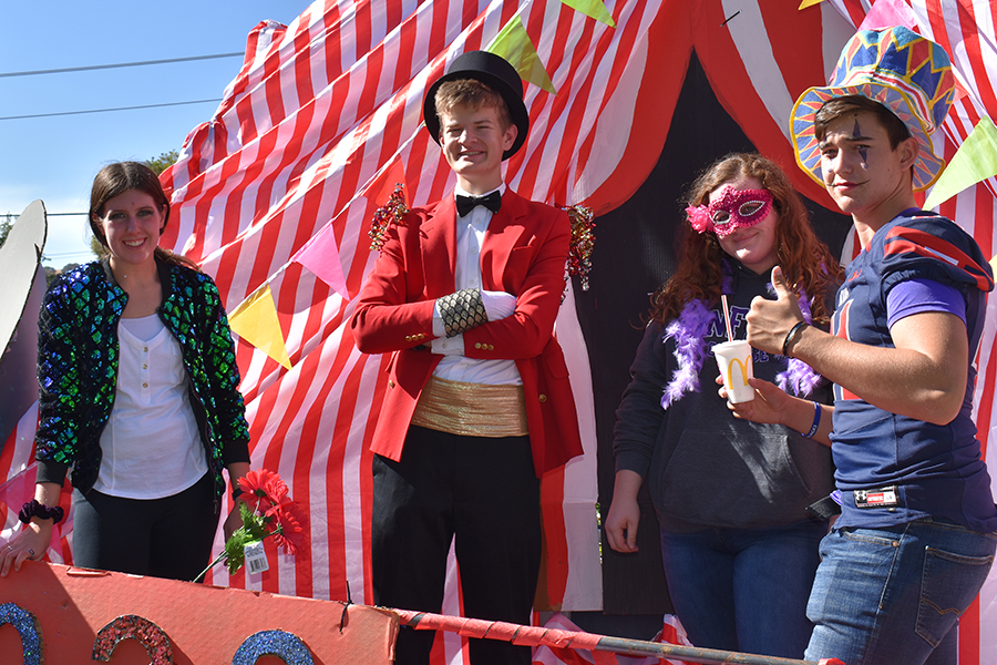 Sophomores Elaina Craig, Daniel lJacobs, Katie Stanek and Bryce Pazdel ride theri Circus Performer-themed float for the Homecoming parade, which ran through the whole school October 25.