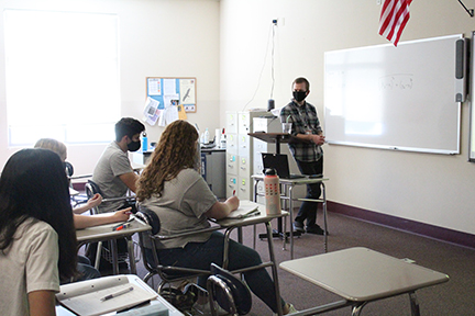 Mr. Andrew Wilson teaches his AP Calculus AB students including Rohan Aujla and Katie Stanek. His laptop, microphone, and camera are set up below his podium.