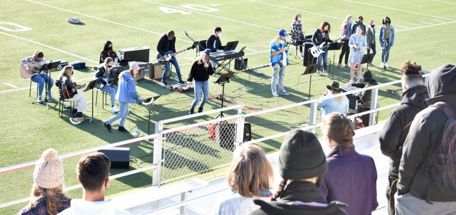 Students and teachers stand in the bleachers and worship along with the Chapel Leadership Team during Easter chapel on March 30, 2021.