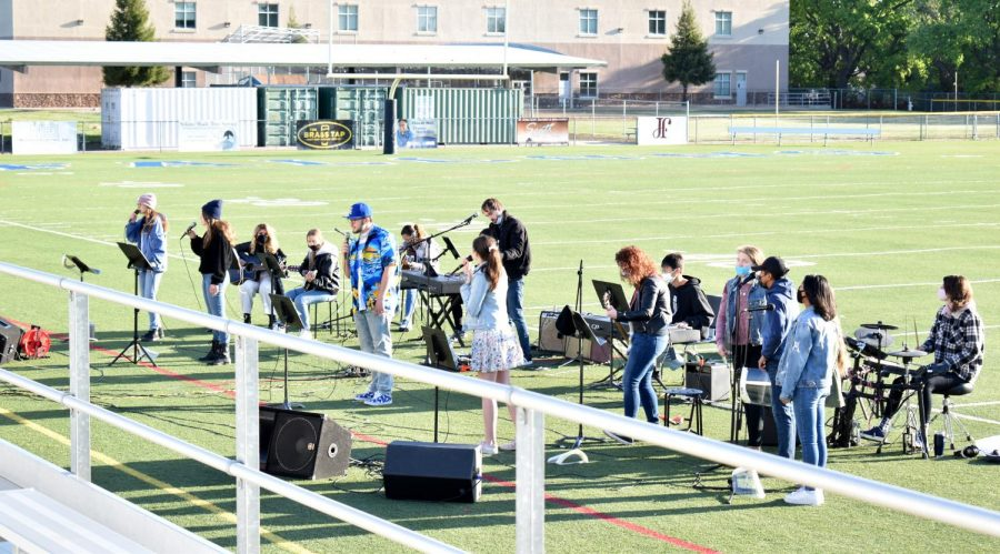 The combined Chapel Leadership Team made up of high school and middle school students, and guest artist Mason whom is a friend of Mrs. Strickland, perform worship songs on the field during chapel on March 30, 2021.