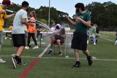 Freshman contestant Silas Jones is sprayed with a water gun for answering a question wrong during the newly wed game during the prom rally on May 20, 2021.