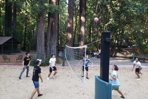 Six students play volleyball at retreat during free time.